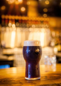 single dark beer sitting on bar